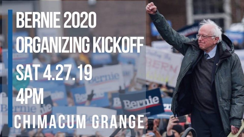 White letters on the left of the image announce the Bernie Sanders campaign kickoff at the Chimacum Grange. On the right of the image Bernie Sanders stands with a determined look on his face and his fist raised in solidarity with a large crowd in front of the stage.